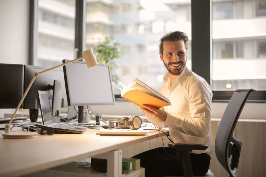 Man smiling sitting at desk working in front of a computer