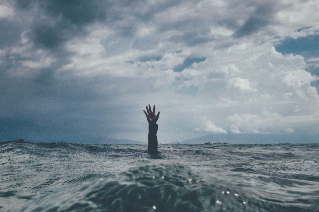 Hand reaching out of the water symbolizing reaching out for help with depression.