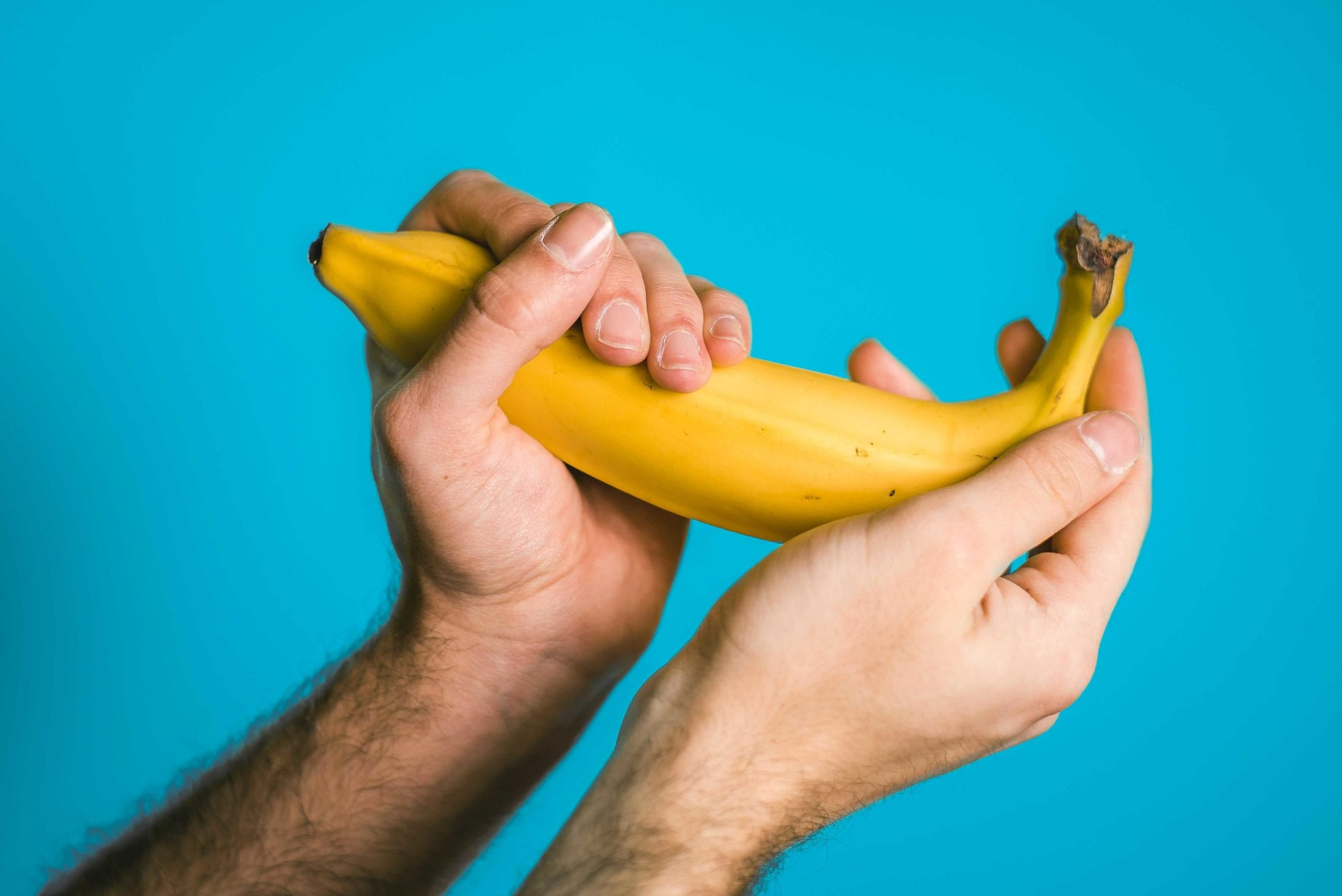Man's hands holding a banana, shaped like a penis, depicting erectile dysfunction.