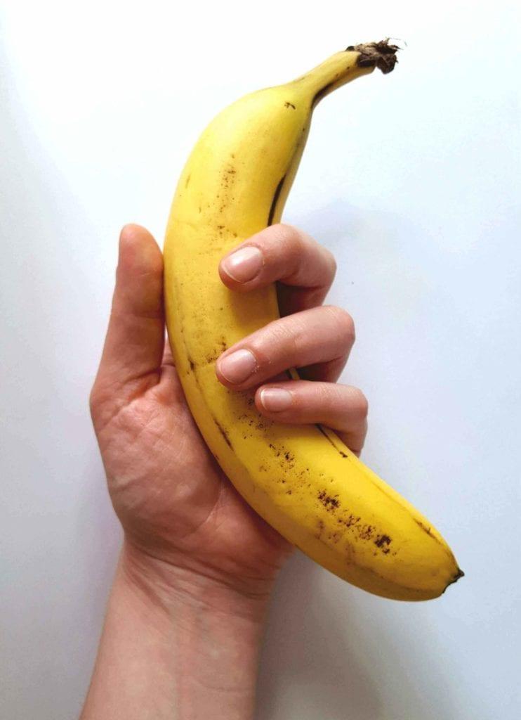 Man's hand holding a banana, depicting erectile dysfunction.