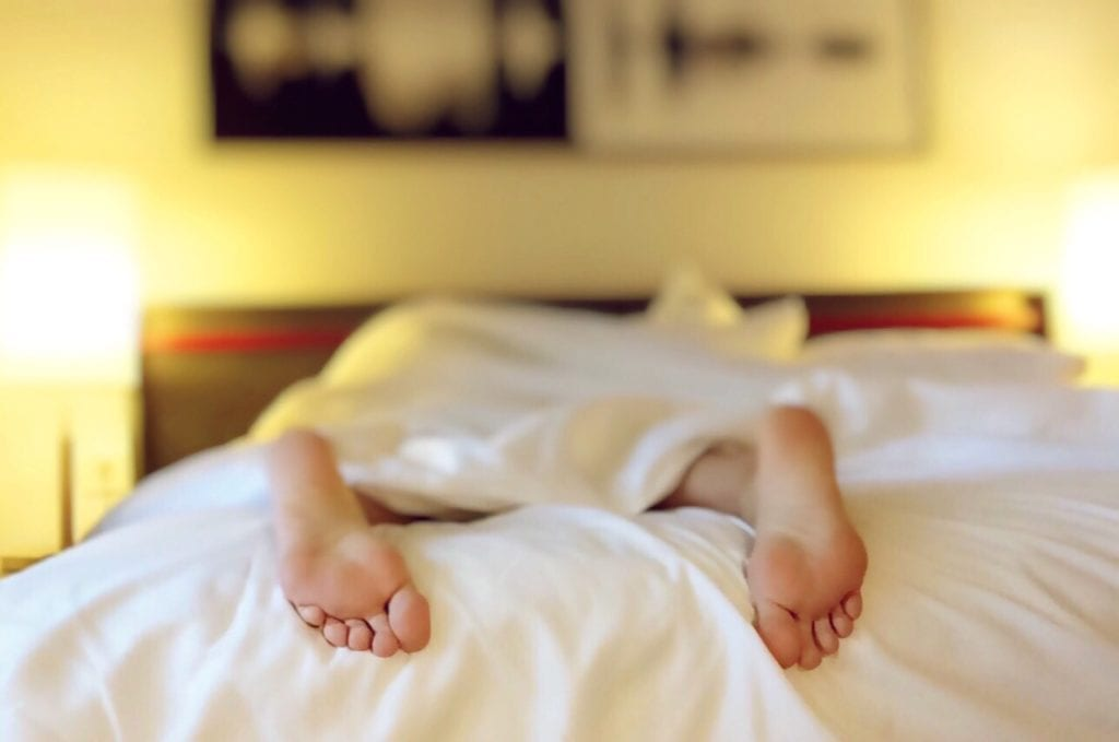 Two feet sticking out of bed. Woman laying face down in bed, all that is visible is her feet sticking out of the white sheets.