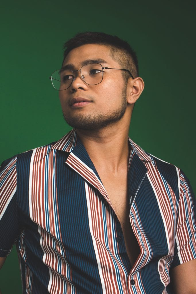 Man with a straight face wearing a striped shirt. He is taking PrEP to prevent HIV standing in front of a green wall.