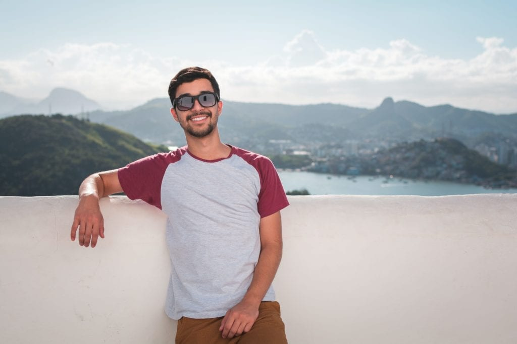 Man smiling who is taking PrEP for HIV standing in front of a mountain view.
