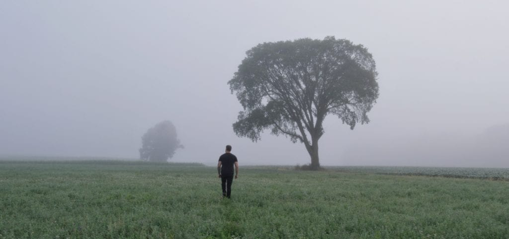 Man walking through a foggy field trying to overcome PTSD
