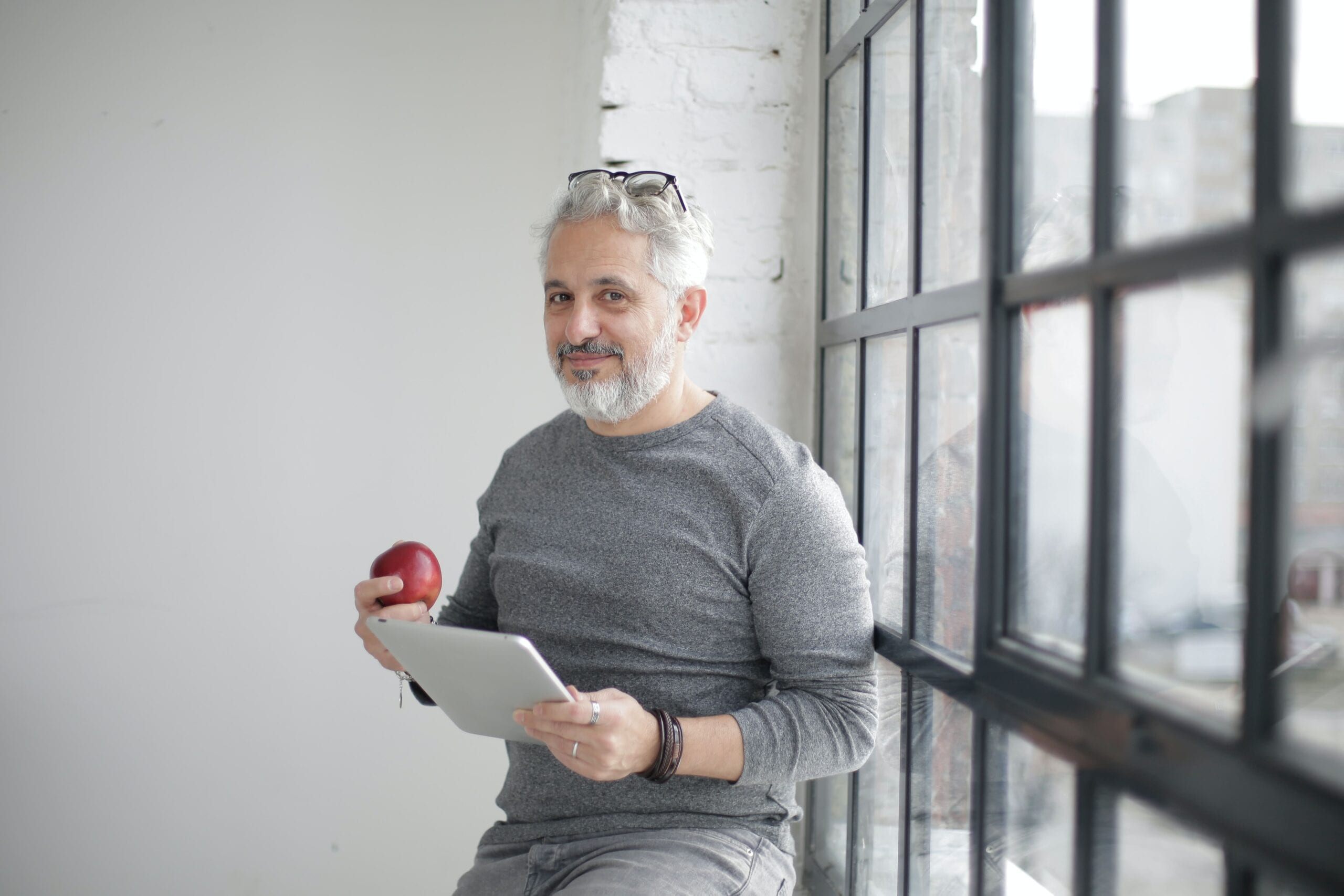 Low testosterone man standing and eating an apple
