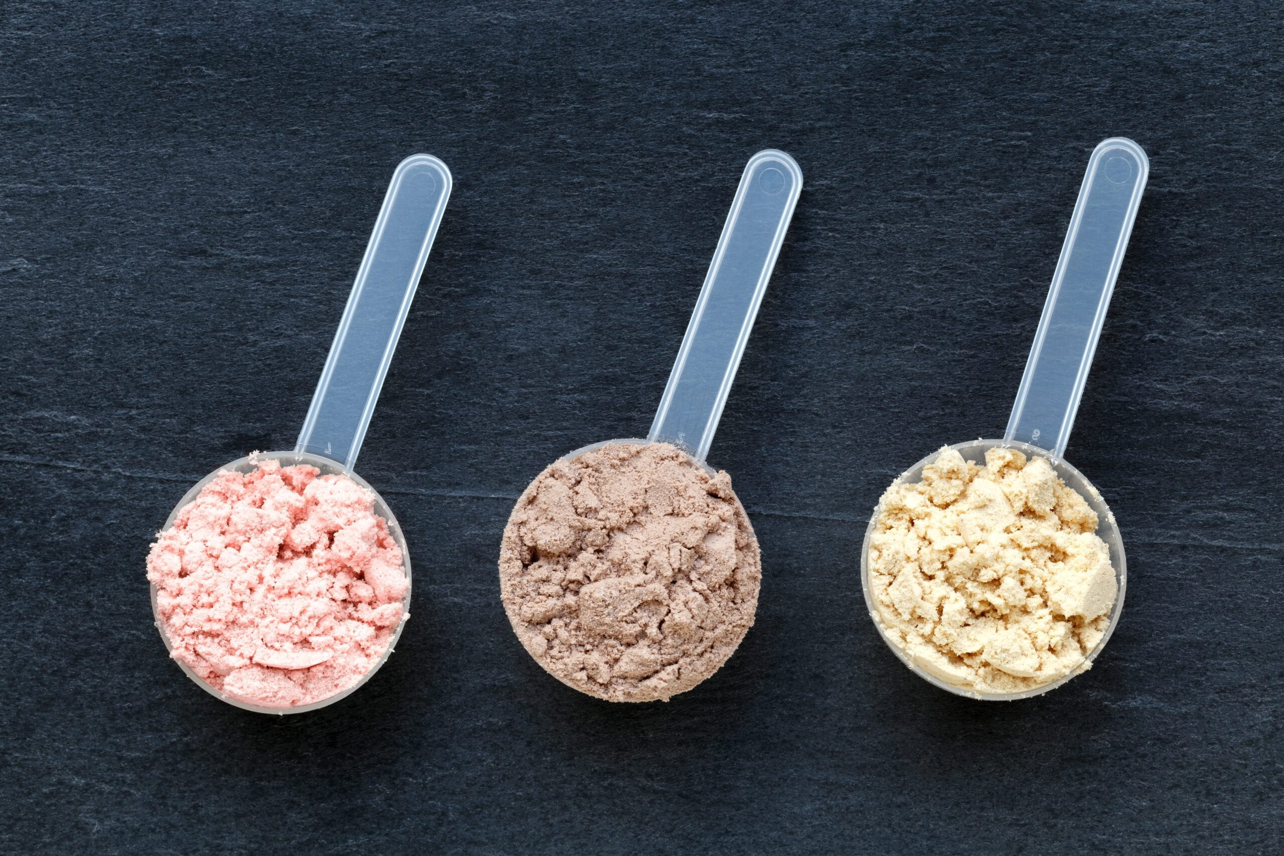 whey protein and collagen protein powders scoops lined up next to each other